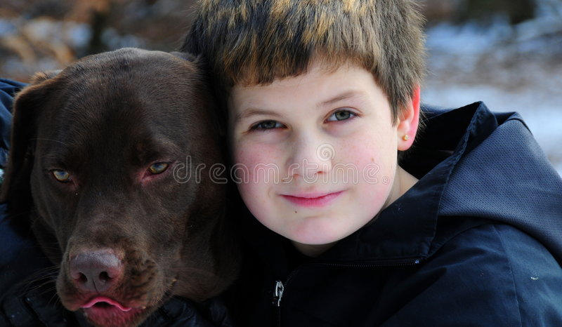Boy and dog. Shot of a boy and a chocolate labrador sharing a hug stock images