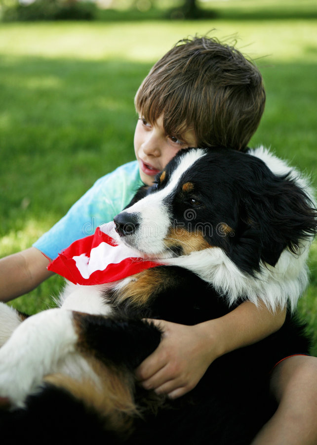 Boy and dog. A boy hugging a dog while sitting on grass