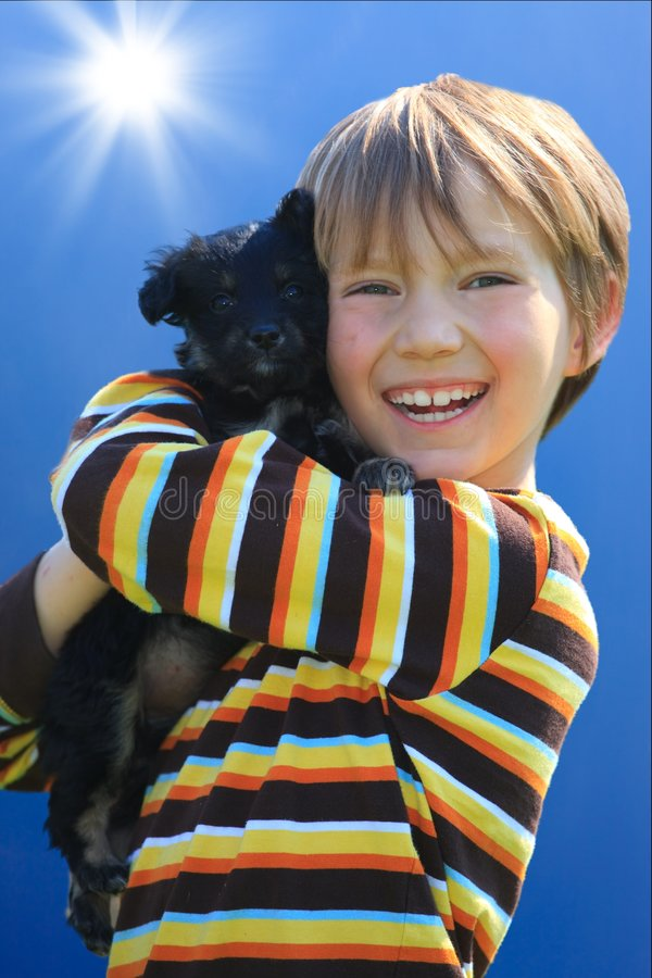 Boy with dog. Little boy shown hugging his pet dog royalty free stock image