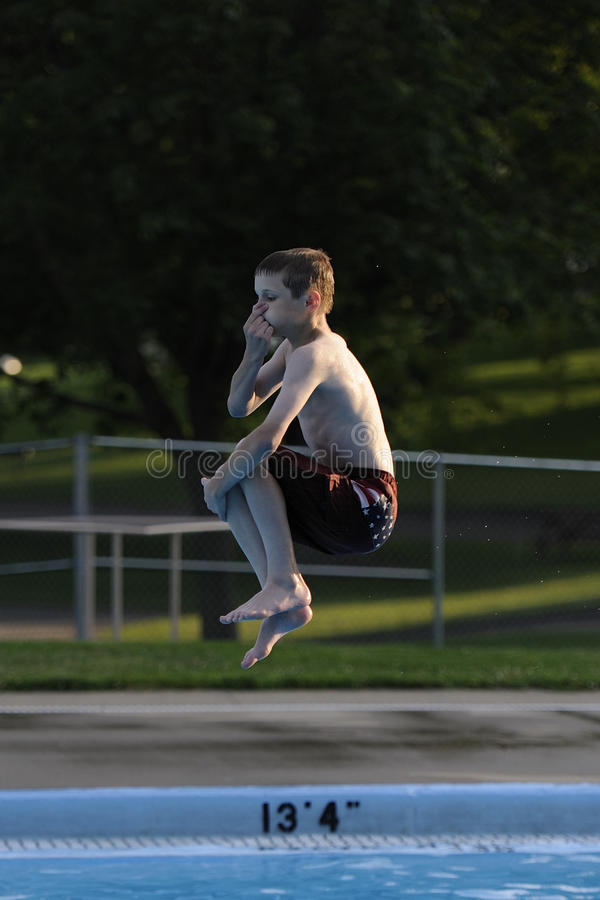 Boy doing cannonball. A boy doing a cannonball from the high dive at the local pool stock image