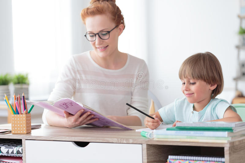 Boy doing exercises from workbook. Math teacher doing exercises from workbook with young happy boy while sitting at desk in classroom stock photos