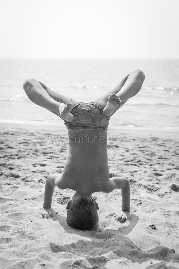 Boy doing a handstand on the beach royalty free stock photo