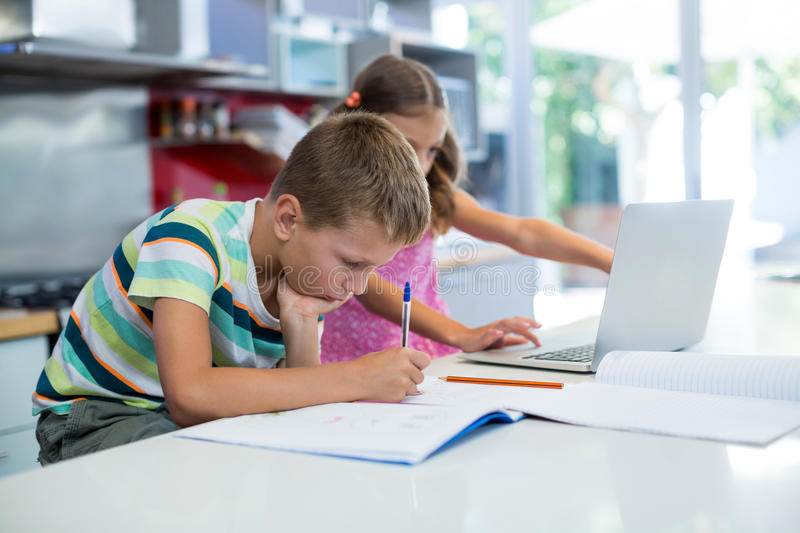 Boy doing his homework while girl using laptop in kitchen. At home stock photos
