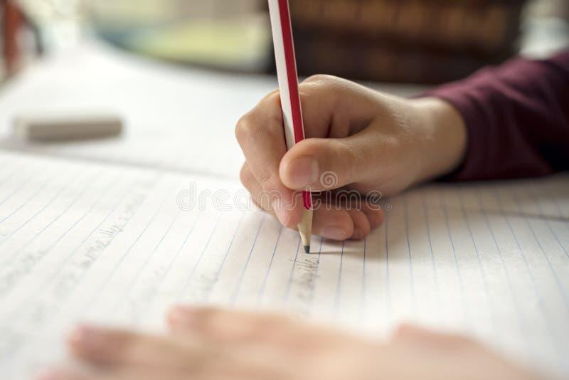 Boy doing his school work or homework. Boy writing in a notepad doing his school work spelling or homework stock photo