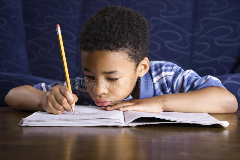 Boy Doing Homework. Young African American boy sitting on the floor in front of a coffee table doing homework. Horizontal shot royalty free stock images
