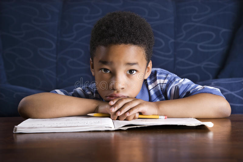 Boy Doing Homework. Young African American boy sits on the floor at a coffee table. He is looking towards the camera with his homework on the table. Horizontal stock images