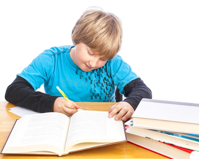 Boy doing homework. Isolated young boy at a table doing homework with books. Space for custom text royalty free stock image