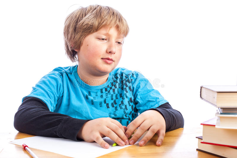 Boy doing homework. Isolated young boy at a table doing homework with books. Space for custom text stock photo