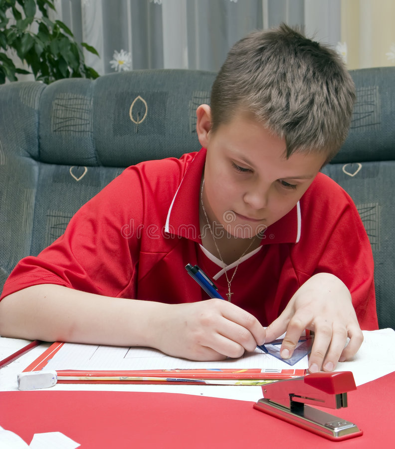 Boy doing homework. A boy doing his homework, art, geometry, mathematics involved, red colour (color) dominating stock image