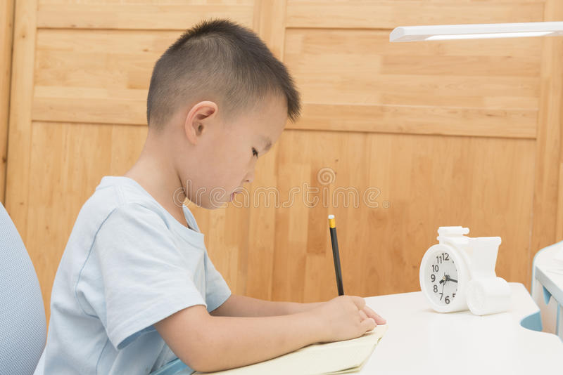 Boy doing homework. Chinese boy doing homework at home royalty free stock photos