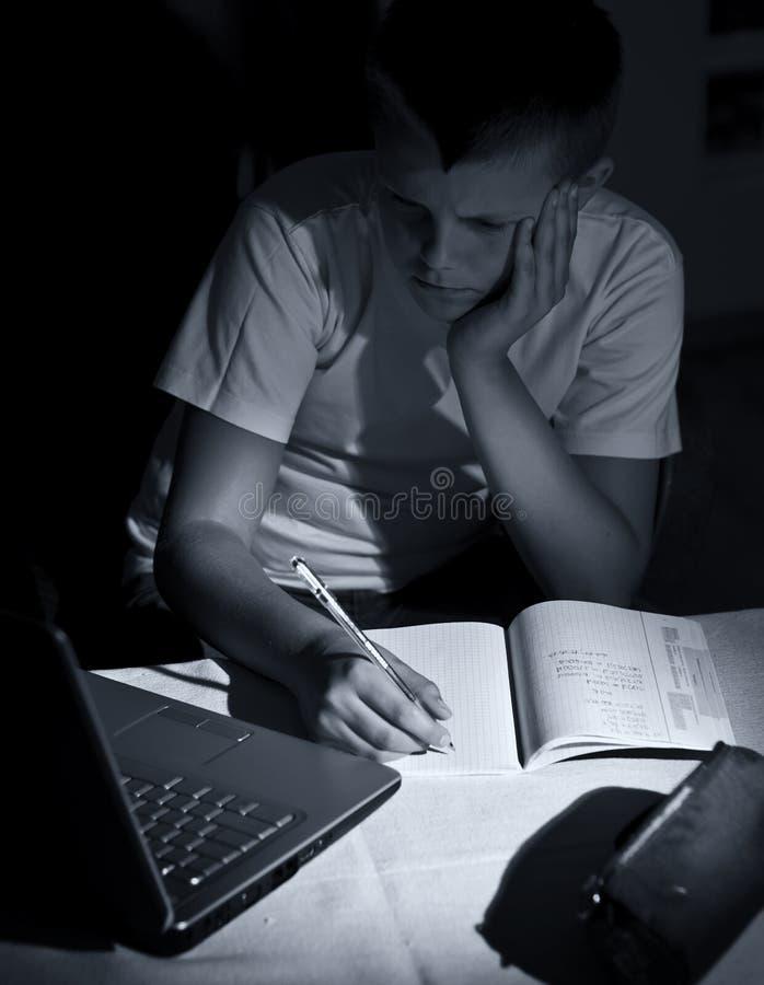 Boy doing homework with laptop