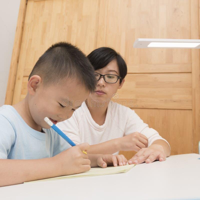 Boy doing homework with tutorship. At home royalty free stock photos