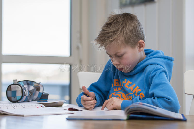 Boy doing homework. Boy writing and doing homework in the kitchen royalty free stock photo