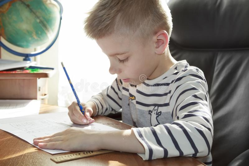 Boy is doing math homework. Kid, child, little, alone, people, person, caucasian, childhood, education, study, learn, school, book, writing, cute, studying stock image