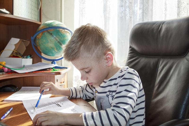 Boy is doing math homework. Kid, child, little, alone, people, person, caucasian, childhood, education, study, learn, school, book, writing, cute, studying stock photo
