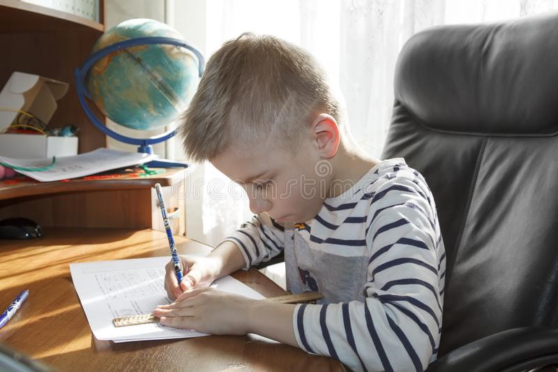 Boy is doing math homework. he draws a pencil on the ruler of the answer to the task. Kid, child, little, alone, people, person, caucasian, childhood royalty free stock images