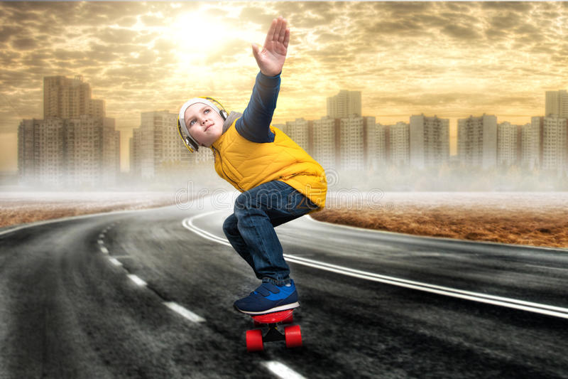 Boy doing tricks on a skateboard,skate on the road.The little boy in the style of Hip-Hop .The Young Rapper.Cool rap DJ. Boy doing tricks on a skateboard stock photo