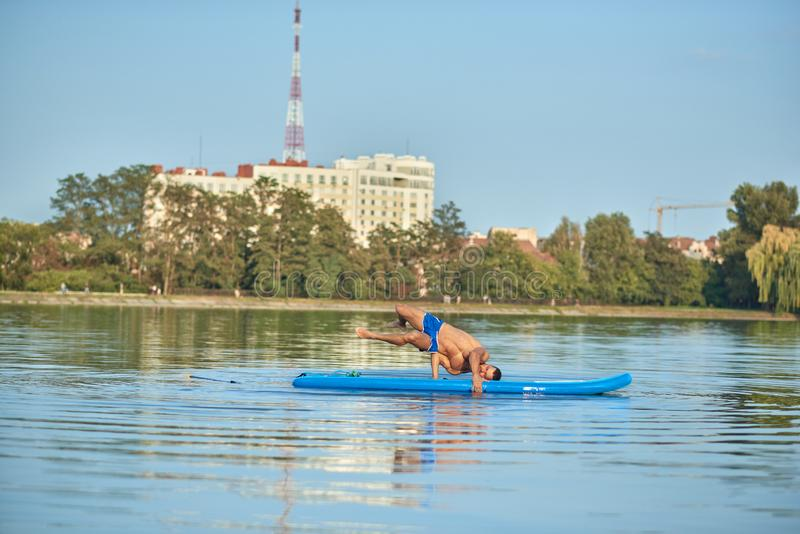 Boy doing yoga exercises while swimming on paddle board in lake. stock images