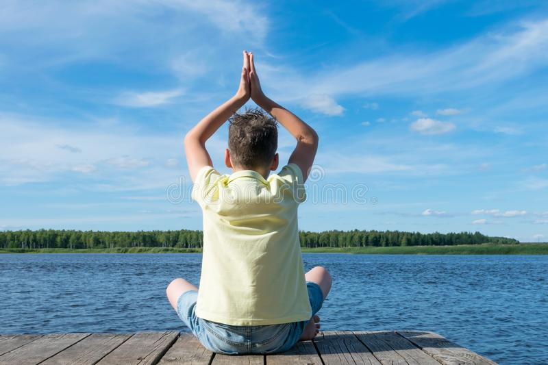 Boy doing yoga in nature by the lake royalty free stock images