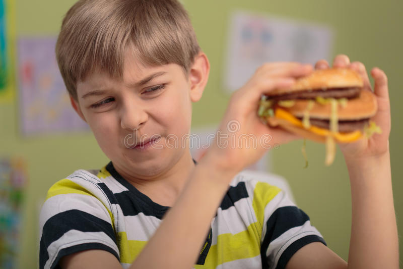 Boy don't like hamburger royalty free stock photography