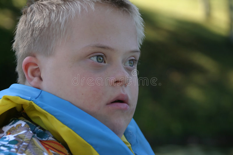 Boy With Down Syndrome. A young boy with down syndrome wearing a life jacket on a boating trip. Wide eyed with anticipation stock photography