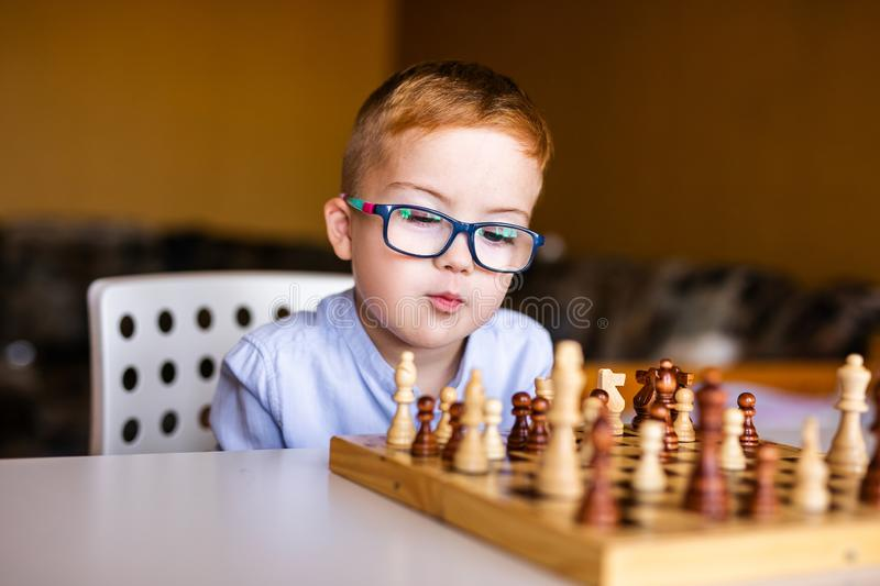 Boy with down syndrome with big blue glasses playing chess in kindergarten.  stock photography