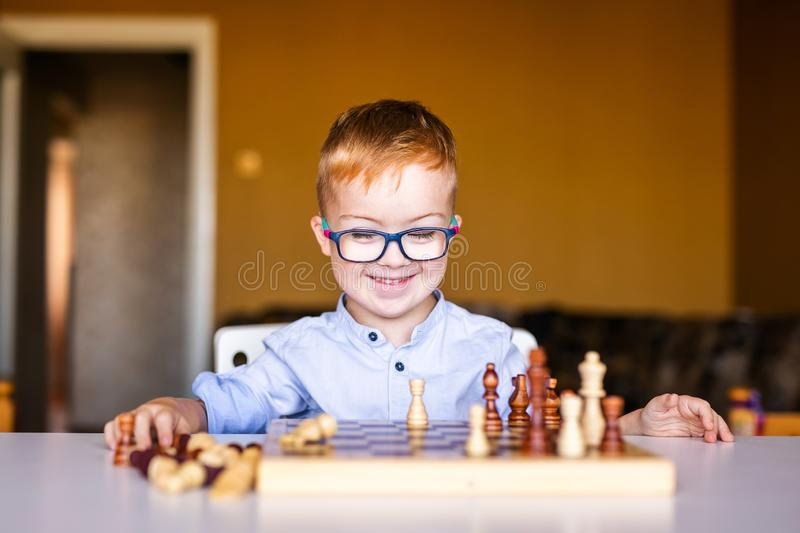Boy with down syndrome with big glasses playing chess.  royalty free stock photography