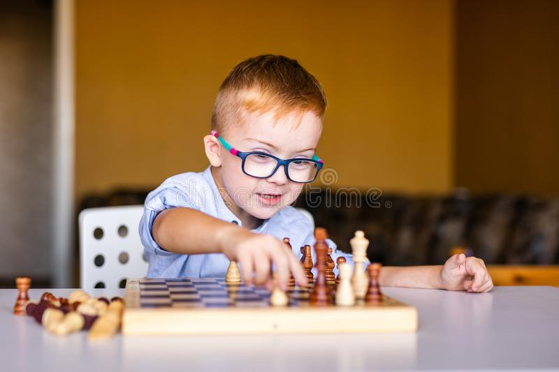 Boy with down syndrome with big glasses playing chess.  stock image