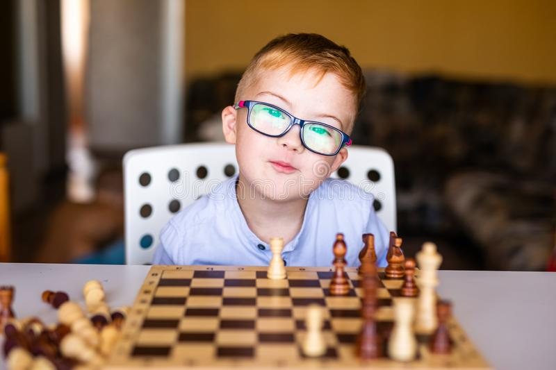 Boy with down syndrome with big glasses playing chess.  stock photos