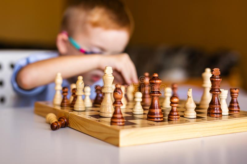Boy with down syndrome with big glasses playing chess.  royalty free stock photos