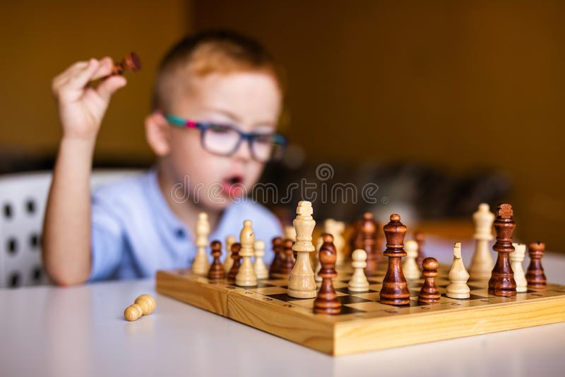 Boy with down syndrome with big glasses playing chess.  stock photo