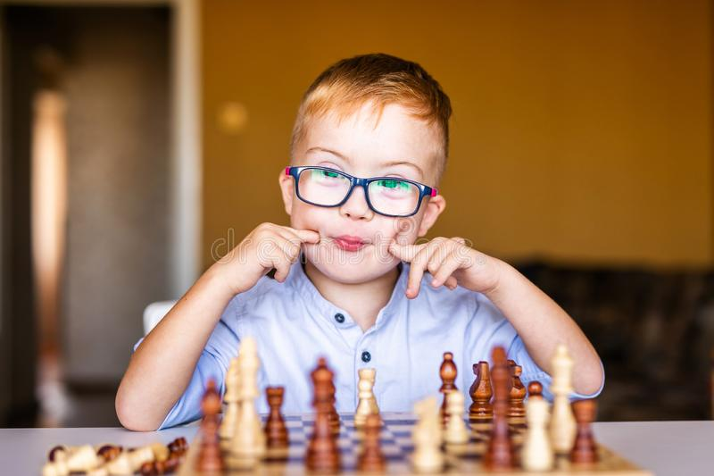 Boy with down syndrome with big glasses playing chess.  stock photography