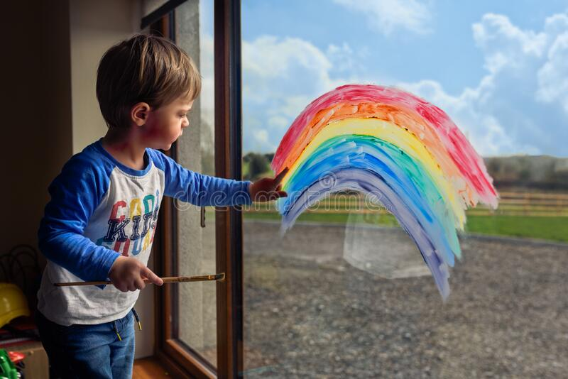 Boy drawing rainbow on the window. Children`s rainbow windows spreading hope amid coronavirus. indoor activities with children royalty free stock photography