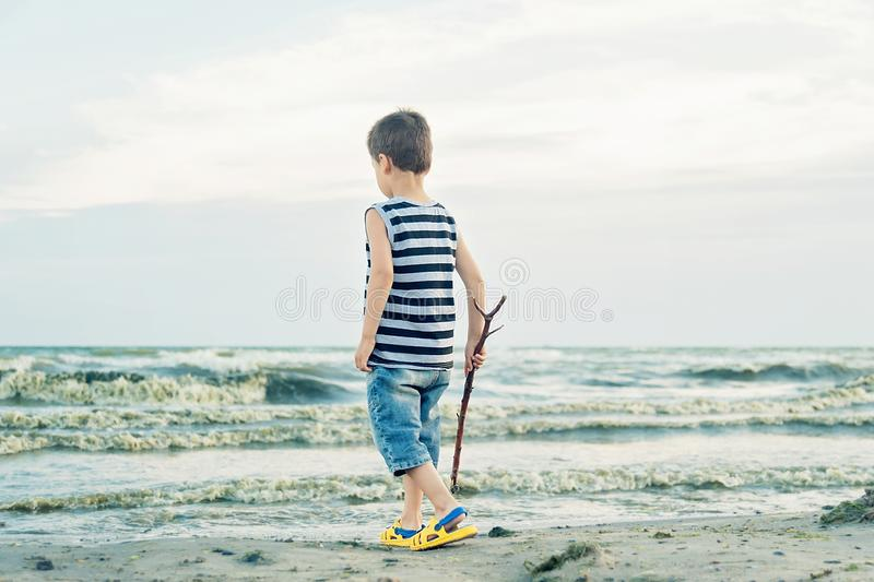 Boy drawing on sand at seaside. Child drawing sand by imaginary on beach for learning stock photo