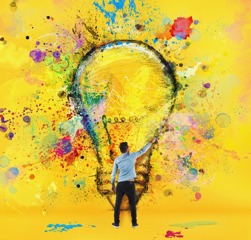 Boy draws with a brush a big light bulb. Concept of innovation and creativity. Yellow style royalty free stock photography