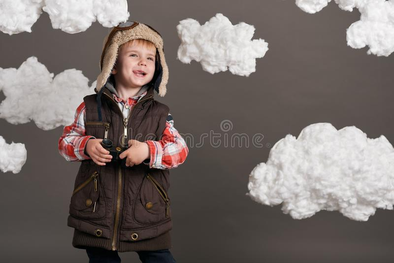 Boy dressed as an airplane pilot stands between the clouds and looks through binoculars stock photography