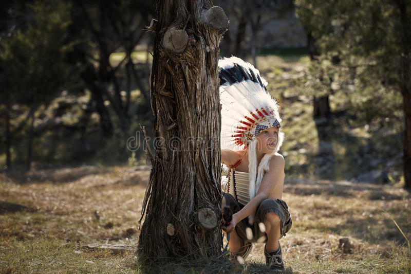 Boy dressed as American Indian. Young boy playing in traditional American Indian headdress royalty free stock image