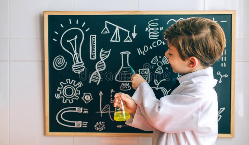 Boy dressed as chemist pointing at blackboard. Smiling boy dressed as chemist with flask pointing at a blackboard with drawings royalty free stock images
