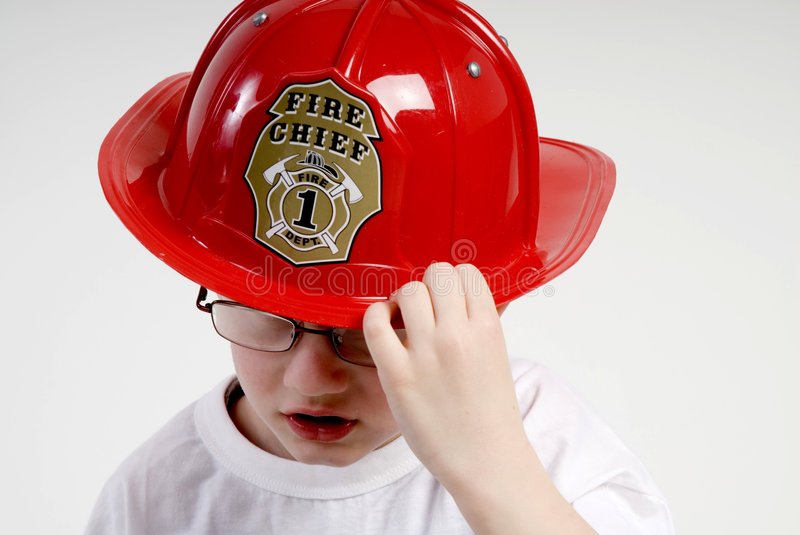 Boy is dressed as fireman. With a helmet royalty free stock image