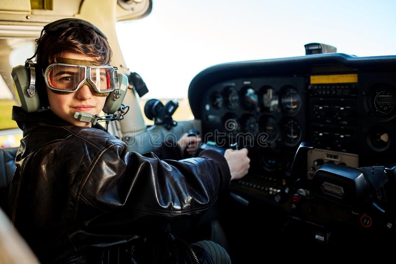 Boy dressed in large pilot jacket, headset and aviator glasses, sitting in cockpit royalty free stock photos