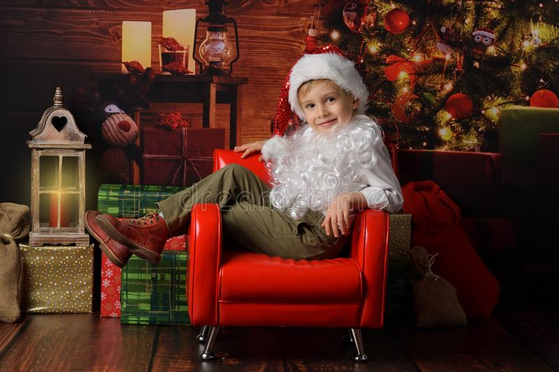 Boy dressed in Santa Claus`s Christmas stock photo
