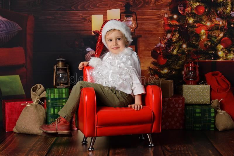 Boy dressed in Santa Claus`s Christmas stock images