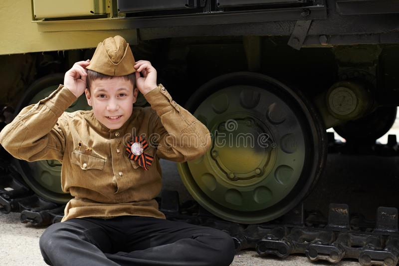 Boy dressed in Soviet military uniform during the second world war posing near army tank stock image