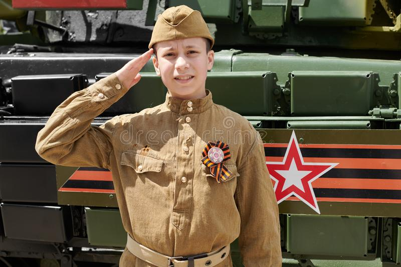 Boy dressed in Soviet military uniform during the second world war posing near army tank stock photos