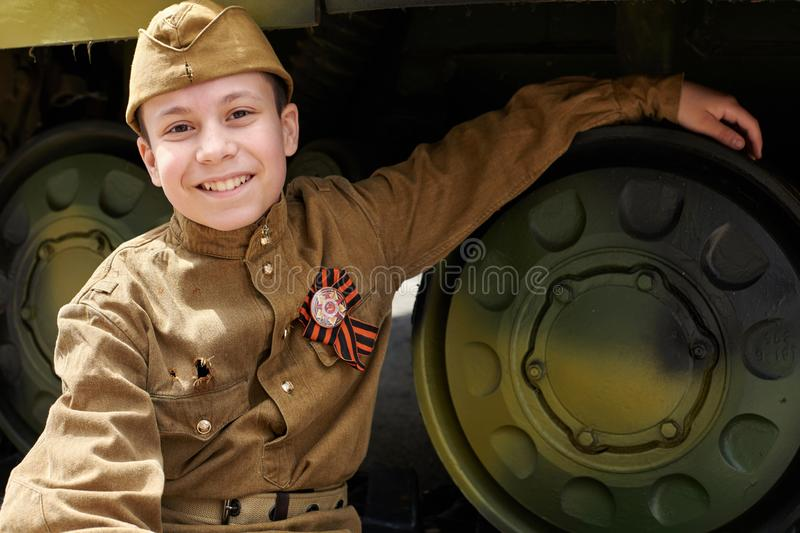 Boy dressed in Soviet military uniform during the second world war posing near army tank royalty free stock photography