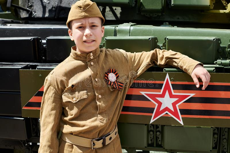 Boy dressed in Soviet military uniform during the second world war posing near army tank stock photography