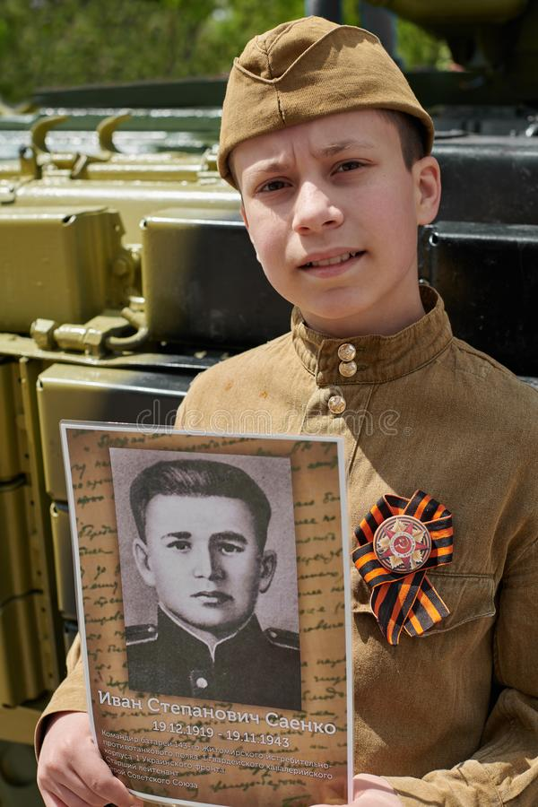 Boy dressed in Soviet military uniform during the second world war posing near army tank and holds portrait his grandfather who. Fought and was a war hero royalty free stock photo