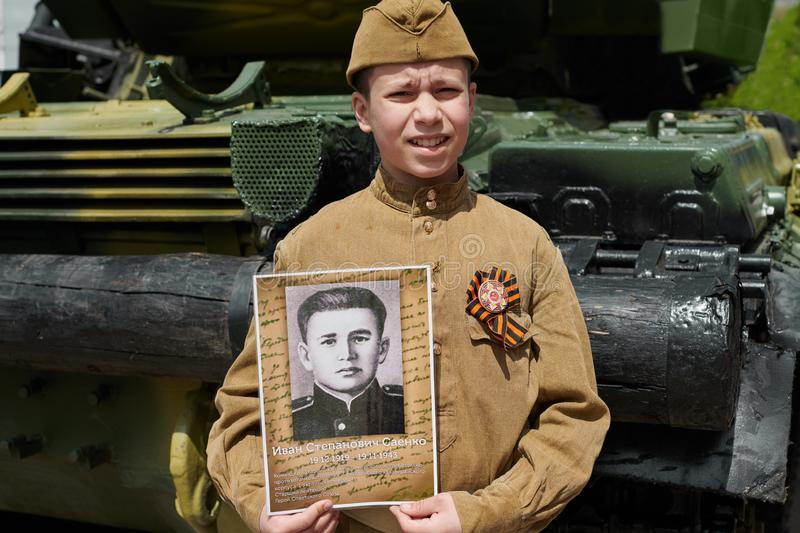 Boy dressed in Soviet military uniform during the second world war posing near army tank and holds portrait his grandfather who. Fought and was a war hero stock photo
