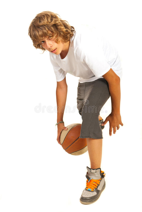 Boy dribbling basketball. Young boy dribbling basketball isolated on white background royalty free stock photo