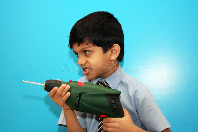 Boy with drilling machine. Young boy playing with drilling machine royalty free stock images